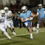 Junior Griffin Fries runs the ball past Blue Valley North players. Photo by Aislinn Menke