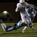 Junior Tyler Stottle tackles the Blue Valley North running back during a play. Photo by Aislinn Menke