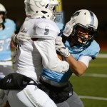 Junior Isaiah Wright holds back the Blue Valley North's quarterback from scoring a touchdown. Photo by Aislinn Menke