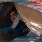 As his boat slowly sinks, Senior Sid Choudhury laughs and sits in his cardboard boat. Photo by Aislinn Menke