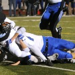 Junior Ryan Hess is tackled while in possesion of the ball. Photo by Izzy Zanone