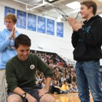 Senior Denny Rice waits while junior Dance Erickson gets the waxing strip ready. Photo by Carson Holtgraves