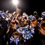 After the Lancer's victory, senior Milton Braasch waves the regional plaque in the air while the football team and cheerleaders cheer together. Photo by Ellie Thoma