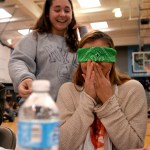 """Senior Grace Chisholm laughs as junior Mallory Frank has a disgusted reaction during """"Guess that Food"""". Photo by Ellie Thoma"""