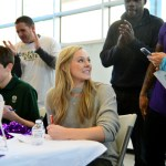Senior Kate Paulus smiles at her tennis coaches while signing her commitment to play at Texas Christian University. Photo by Elizabeth Anderson