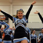 Junior Maggie Gray sticks her arms up in the air as she cheers to the audience. Photo by Katherine Odell