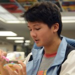Freshman Kai Aken decorates a sugar cookie with blue and pink frosting. Photo by Katherine McGinness