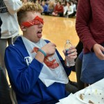Junior Zane Meeks reacts to being fed an unnamed canned food by sophomore Peter Kohring. Photo by Lucy Morantz