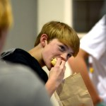 Freshman Charlie McCray eats a hamburger during the wrestling team's presentation. Photo by Luke Hoffman
