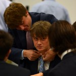 Senior Matt Hogan tightens senior Kristian Jaspersen's tie during dinner. Photo by Luke Hoffman