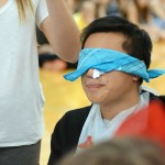 Freshman Luke Tsaur hesitantly tries a food during a blind-fold taste test competition. Photo by Ty Browning