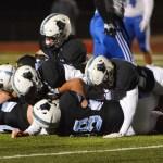 East defensive line men pile onto Olathe Northwest player. Photo by Ava Simonsen