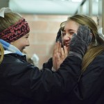 Sophomores Chloe Sowden and Elise Griffith warm up with and warmers in the bathroom during halftime. Photo by Ava Simonsen