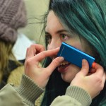 Junior Mckenna Conway puts a portable phone charger up to her face to try to keep warm. Photo by Ava Simonsen