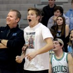 Junior Ryan Hess and Mr. Haney cheer as the student section takes turns shooting 3 pointers during halftime. Photo by Ellie Thoma