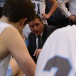 Varsity coach Shawn Hair leads the team in a huddle during a time out. Photo by Reilly Moreland