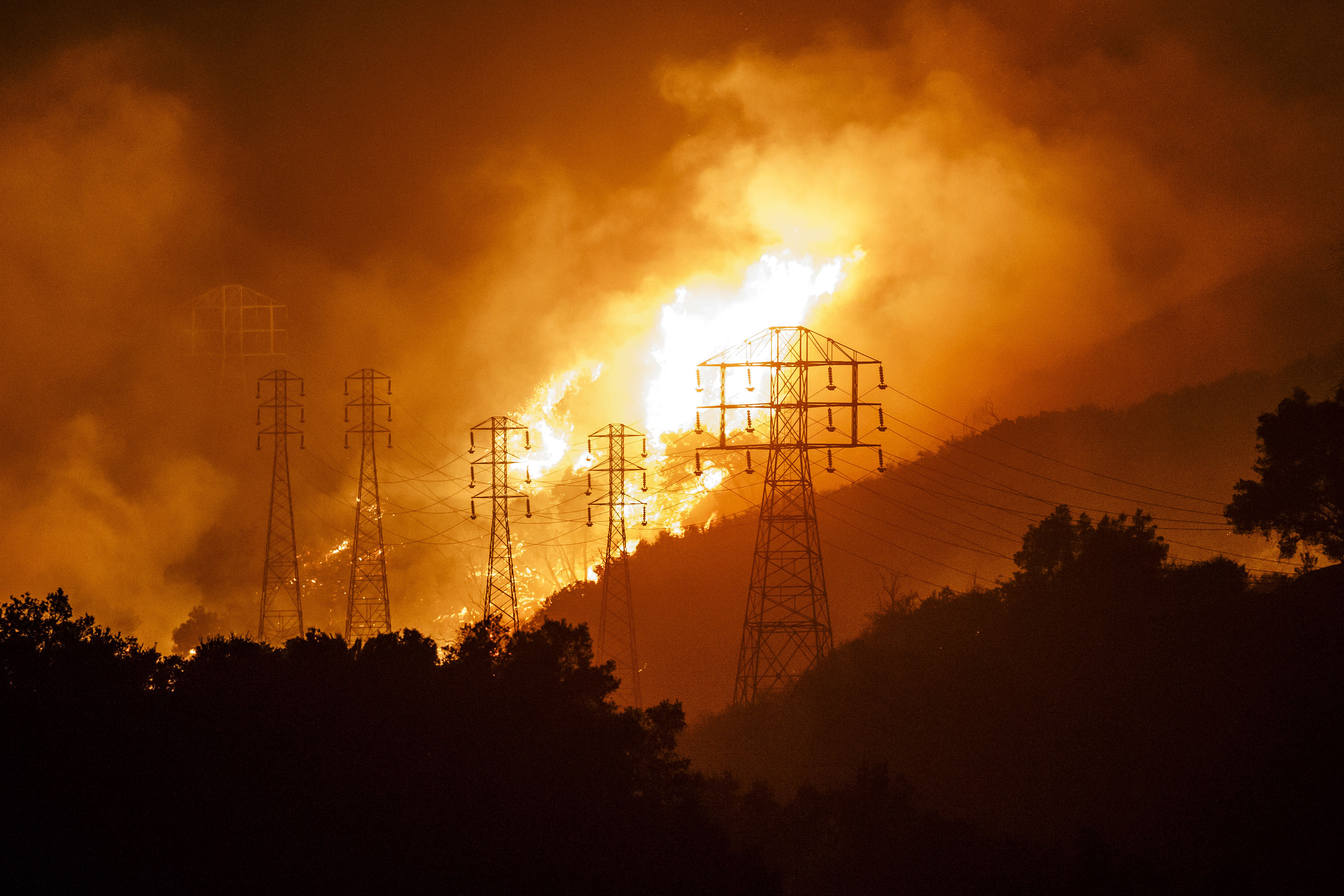 Flames whip around utility power lines as winds drive towards town in Sycamore Canyon threatening structures in Montecito, Calif., on Dec. 16, 2017. (Marcus Yam/Los Angeles Times/TNS)