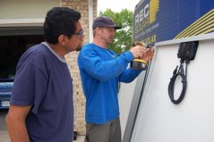 Tim (right) shows Joel how to install the grounding lugs onto each panel.