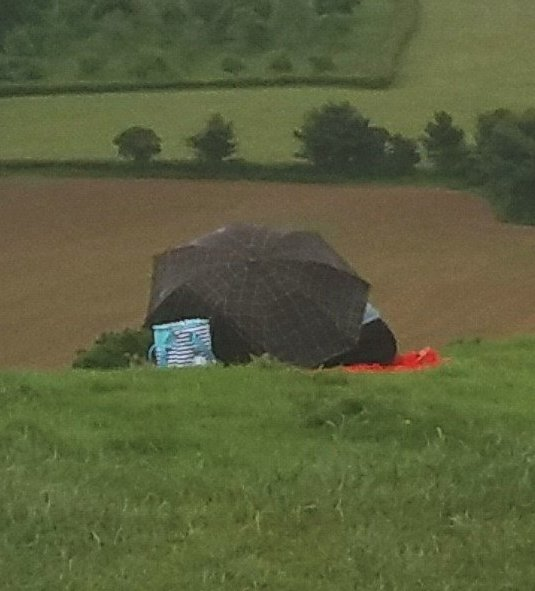 Couple sheltering under an umbrella - Glastonbury Tor 3rd June 2017