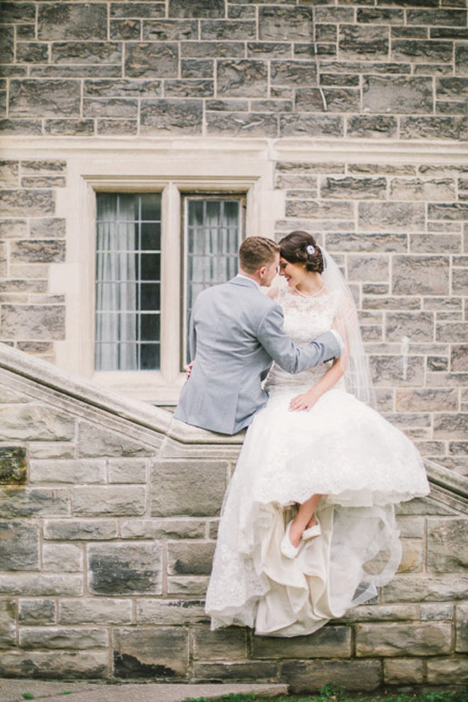 Bride and groom sitting on church wall