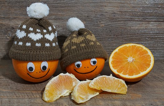 Happy oranges wearing winter hats