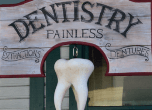 Old wooden sign with text: painless dentistry Extractions Dentures