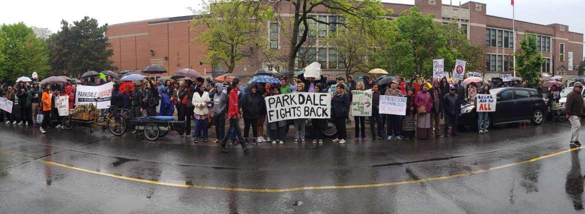 Image of Parkdale Organizers outside the Toronto Food Terminal holding umbrellas in the rain. Signs read Parkdale Fights Back