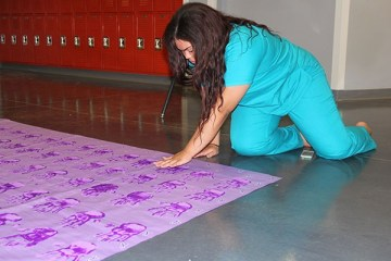 """Senior Karen Santos, Banner and Posters Committee Chair, adds finishing touches to the backdrop for Week of Respect. The backdrop will be in the cafeteria during the event. """"The purpose of the banner is called a """"step and repeat"""" in which students will take photos with the poster as their back drop. As this is done, the students will post the photo on any social media website using the hashtag """"#SOUTHWESTRESPECT"""" and will then have the opportunity to sign their name on one of the handprints,"""" Santos said.  Photo Credit: Alex Nedelcu"""