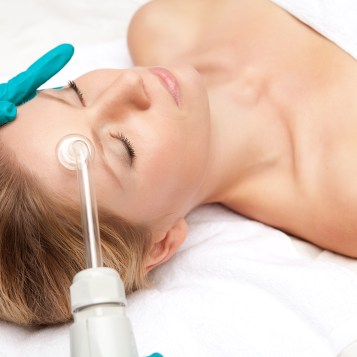 Acne_Skin_Care_Spatique_Overland_Park_66223_oung woman and medical device touching her face