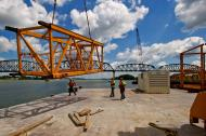 Loading tower mast sections onto transport barge.