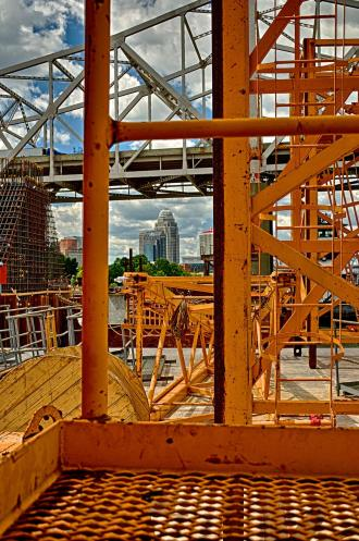 Louisville skyline seen through crane sections on transport barge.