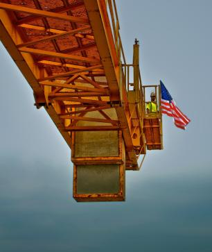 David Graff places the US Flag on the Tower Crane on Pier 5 of the Downtown Span of the Ohio River Bridges Project.