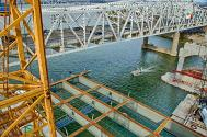 View of the new bridge girders in place as the Walsh Crew Boat delivers workers to the job site.