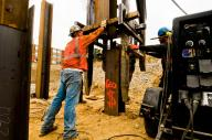 Pile driving crew placing a piling section for welding before driving further into the earth. #2