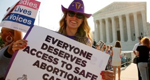 "A demonstrator wearing a cowboy hat with a uterus symbol holds a sign outside the U.S. Supreme Court as the court is set to rule on a legal challenge by abortion providers to a Texas law requiring doctors performing the procedure to have ""admitting privileges"" at local hospitals and clinics to meet hospital-grade standards in Washington, U.S. June 27, 2016. REUTERS/Kevin Lamarque"