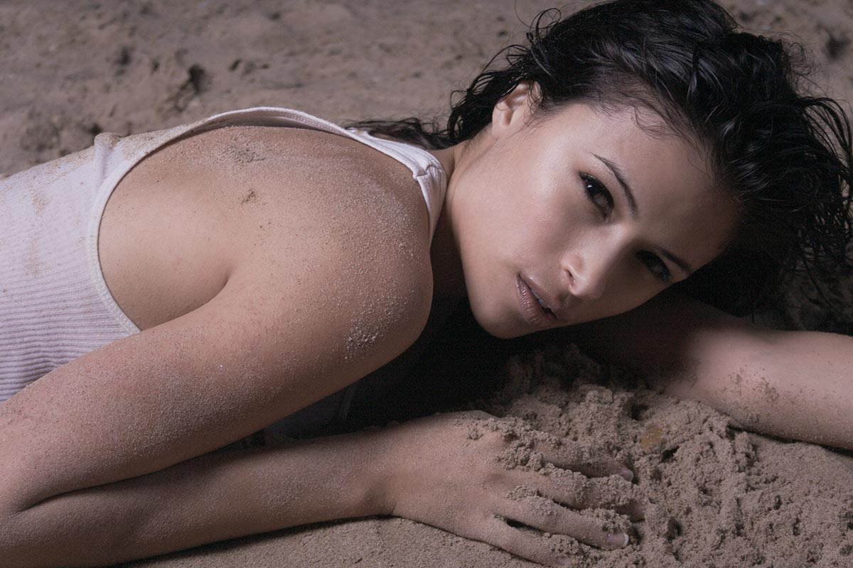 Sultry female model laying in the sand original photograph