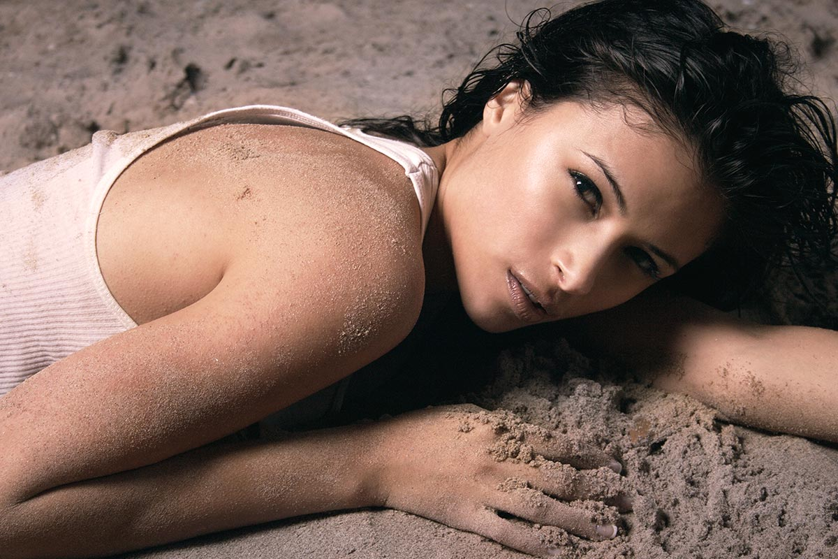 Sultry female model laying in the sand retouched photograph