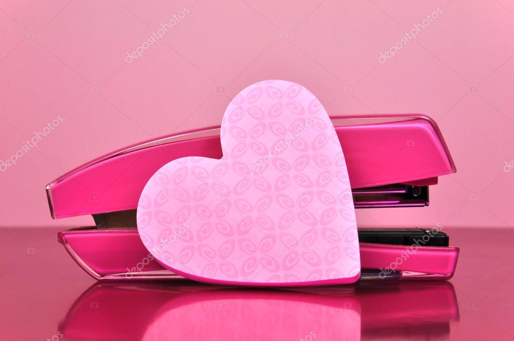pretty in pink office accessories stapler and heart shaped post it note pad paper on a desk against pale background u2014 photo by amarosy feminine o