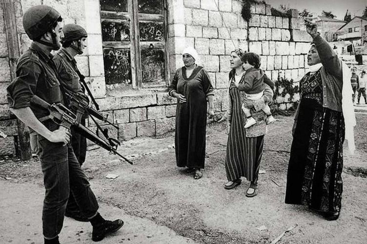 Women seen confronting Israeli troops in Gaza during the first intifada. After this photo was taken the women were assaulted and dispersed with truncheons and tear gas. [Robert Croma / maryscullyreports.com]