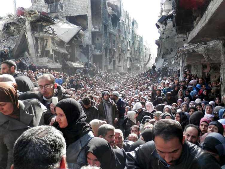 Palestinian refugees shown queuing for food supplies in the Yarmouk refugee camp in 2014 ( AP )