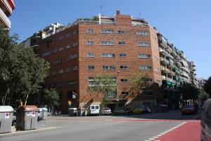 En modern byggnad i L´Eixample visar tydligt hur hörnen på kvarteren skurits av. Till vänster i bilden ser vi sopkärlen som är placerade i ett gatuhörn. Mitt i bilden ser vi hur ett gatuhörn används som parkeringsplats. Foto: Ulf Liljankoski