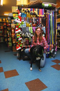 From left, Nancy Fedelem, owner of Fang & Feather, with shop dog Parker. Troy Susan writes an order at the tiki hut inside Bamboo Craftsman. Garland Horner knits bike rack covers for Green Zebra Market, while her dog Vegas looks on.  (Judy Nelson)