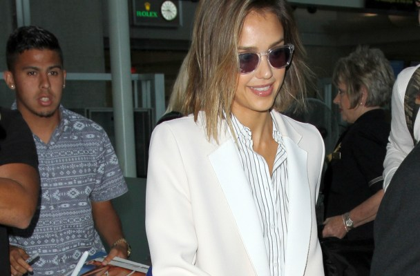 Jessica Alba looks near flawless as she is mobbed by fans upon her arrival in Los Angeles.