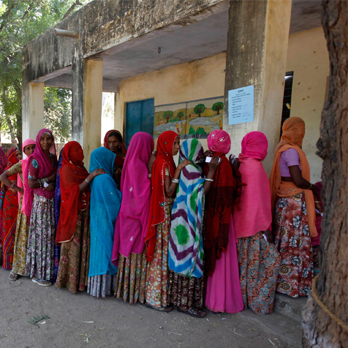 Voters line up in a queue outside a polling booth to cast their vote during the state assembly election in Maval town, located in the desert Indian state of Rajasthan