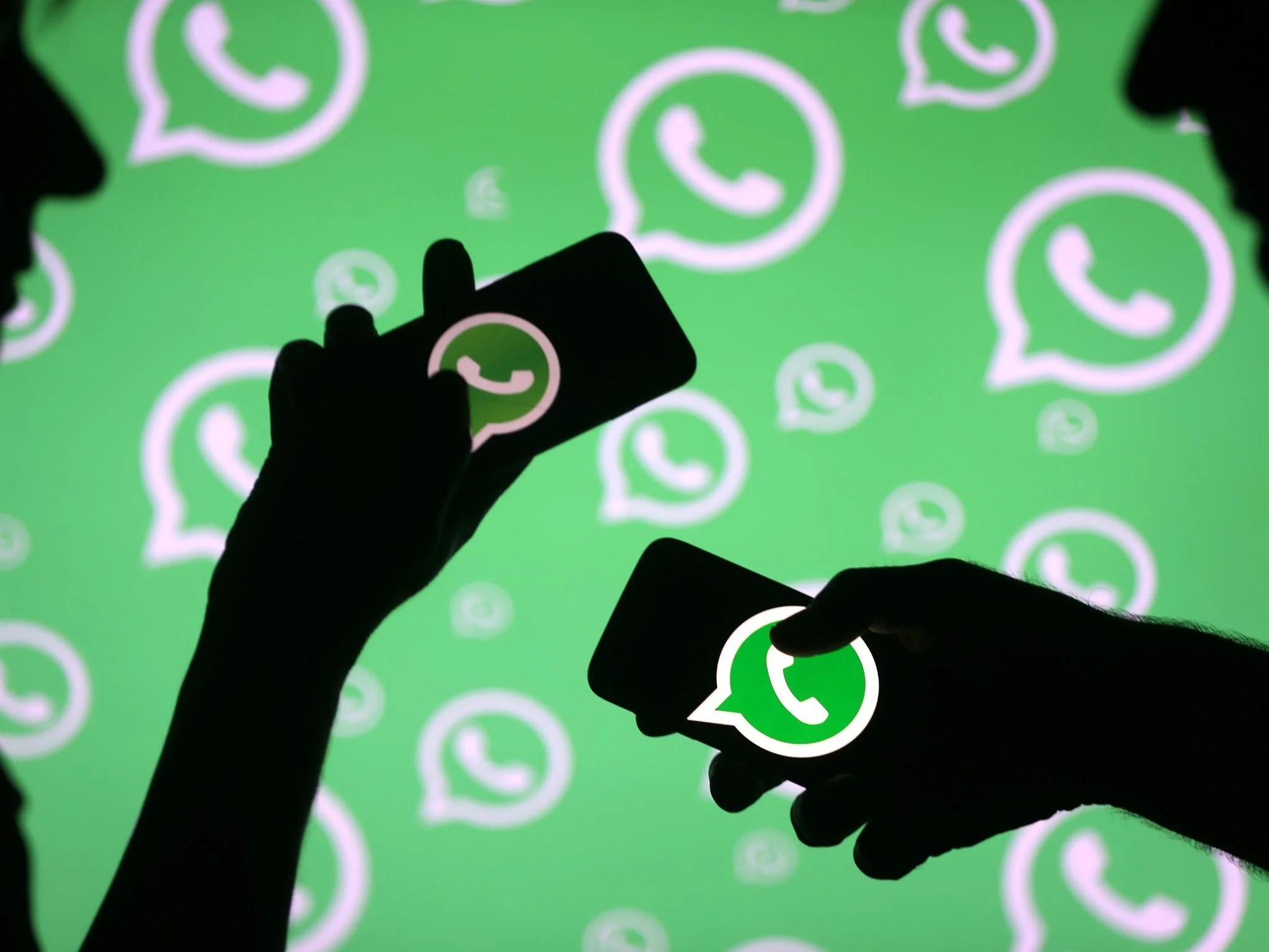 WhatsApp  New feature lets you block notifications you don t care     Men pose with smartphones in front of displayed Whatsapp logo in this  illustration September 14