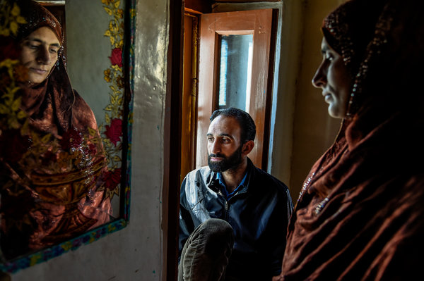 Mohammad Ishaq Lone, 39, with his wife, Sumaya Ishaq, at his house in Rawalpora, Kashmir. Mr. Lone said Indian Army soldiers detained and beat him in February.
