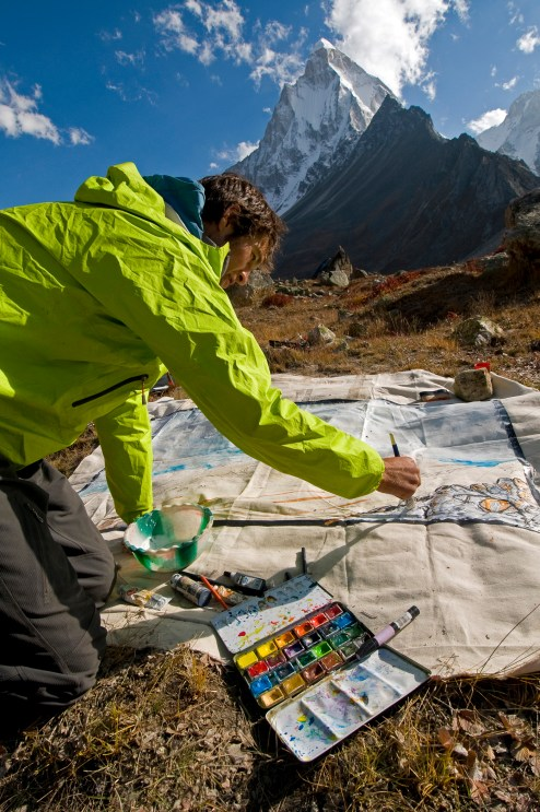 Artist Renan Ozturk painting at basecamp before the 2008 Meru attempt.