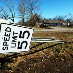 February 8, 2008, Polk County, AR -- Highway sign bent by tornado which swept the state. Church volunteers in the bacground attempt to salvage valuables from house which was destroyed.  The Federal Emergency Managment Agency (FEMA) works closely with volunteer agencies to provide much needed help in the immediate aftermath of a disaster. Leif Skoogfors/FEMA