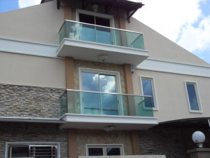 cream-and-stone-wall-house-with-glass-balcony-with-glasses-windows-can-add-the-modern-touch-inside-house-it-also-has-cream-fence-in-front-of-the-house