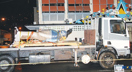 The statue lying in a mummy like state about to be resuscitated as it arrived on Peynier Street Wednesday night. It was later mounted at around 12:30 AM. – Photo by Lucius Doxerie.